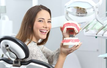 Young Woman in Dentist Chair Holding Model of Teeth Philadelphia PA
